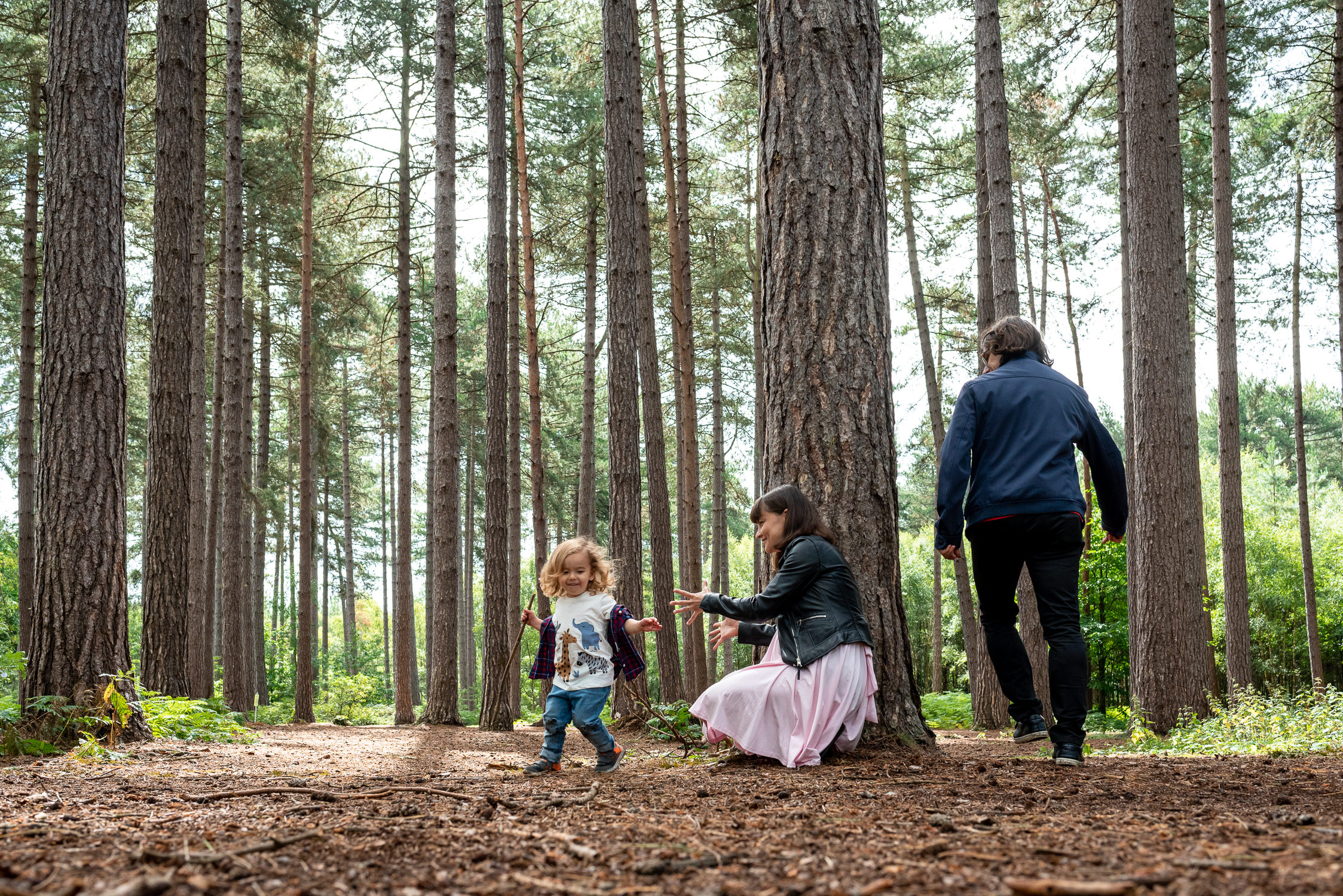 family playing hide and sheek on a family photoshoot in Black Park