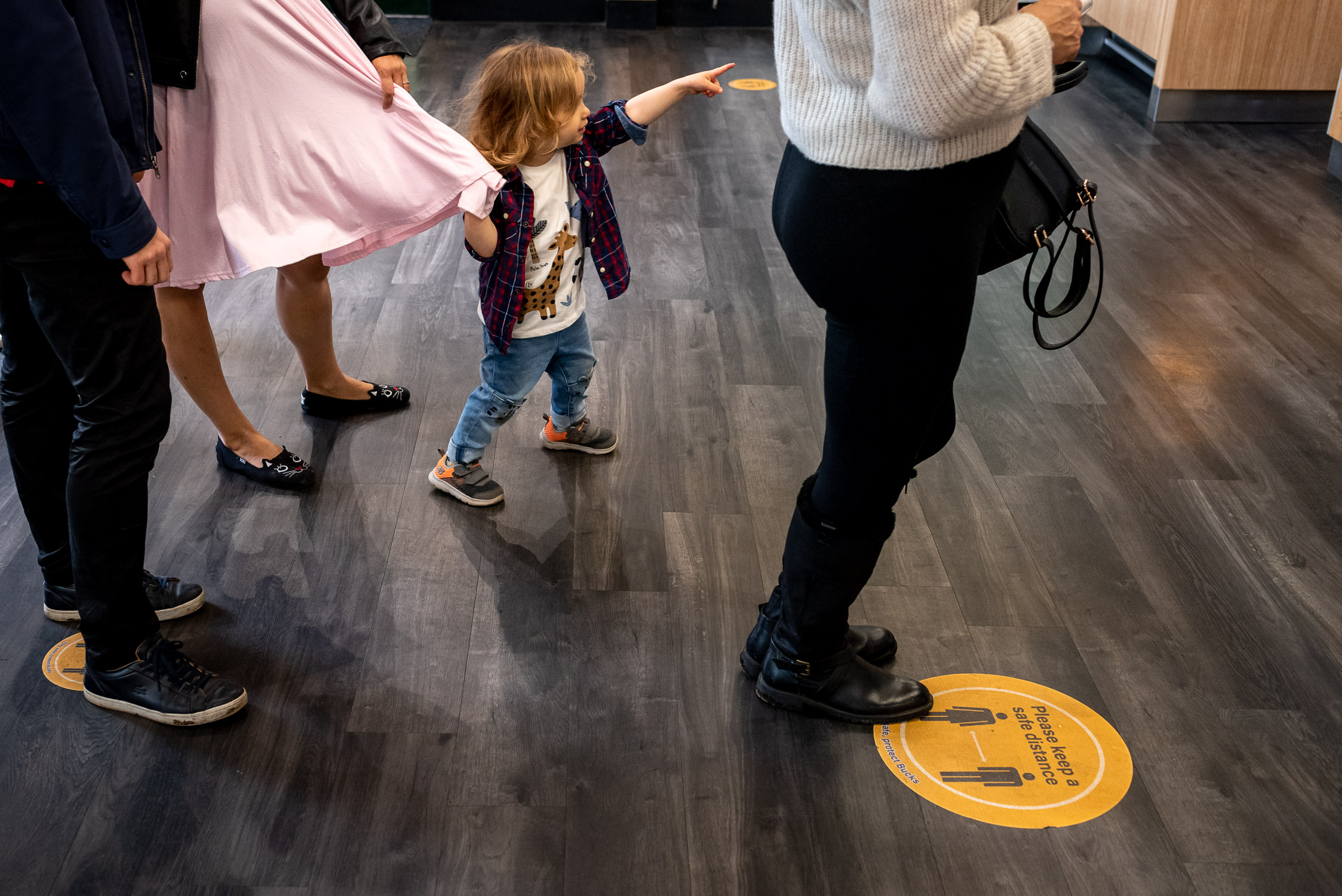 socially distanced sign on floor with family